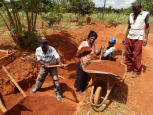 Members of the Luchululu Community Unit in Samia Subcounty make interlocking bricks used in constructing durable toilets.