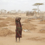 A young girl stands amid the freshly made graves of 70 children many of whom died of malnutrition. Dadaab refugee camp.