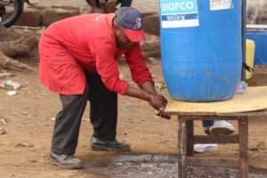 John Otieno a Kibera resident washes hands at a community hand washing station at Kamkunji grounds in Kibera-