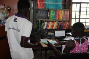 A Form Three student borrows a book from the Amani Kibera Library in Lindi, Kibera.