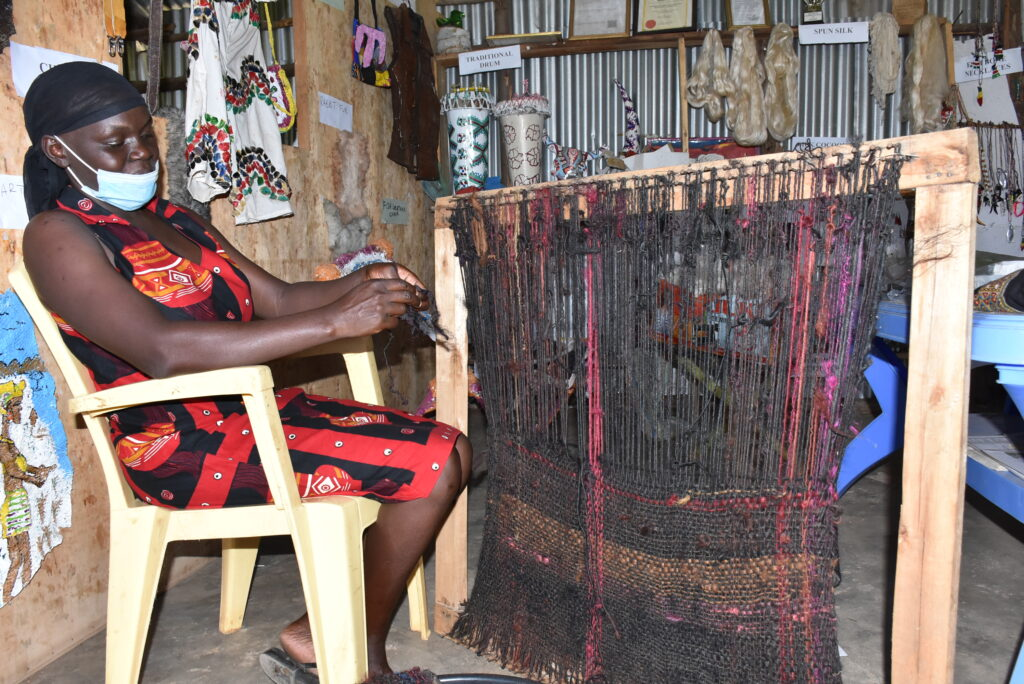 Sarah Adero, a mother of four knits a carpet from recycled waste human hair. She is among the women who are collecting wigs, weaves and used braids to transform them into carpets and mats as part of an effort to reduce environmental pollution. PHOTO: Viola Kosome.
