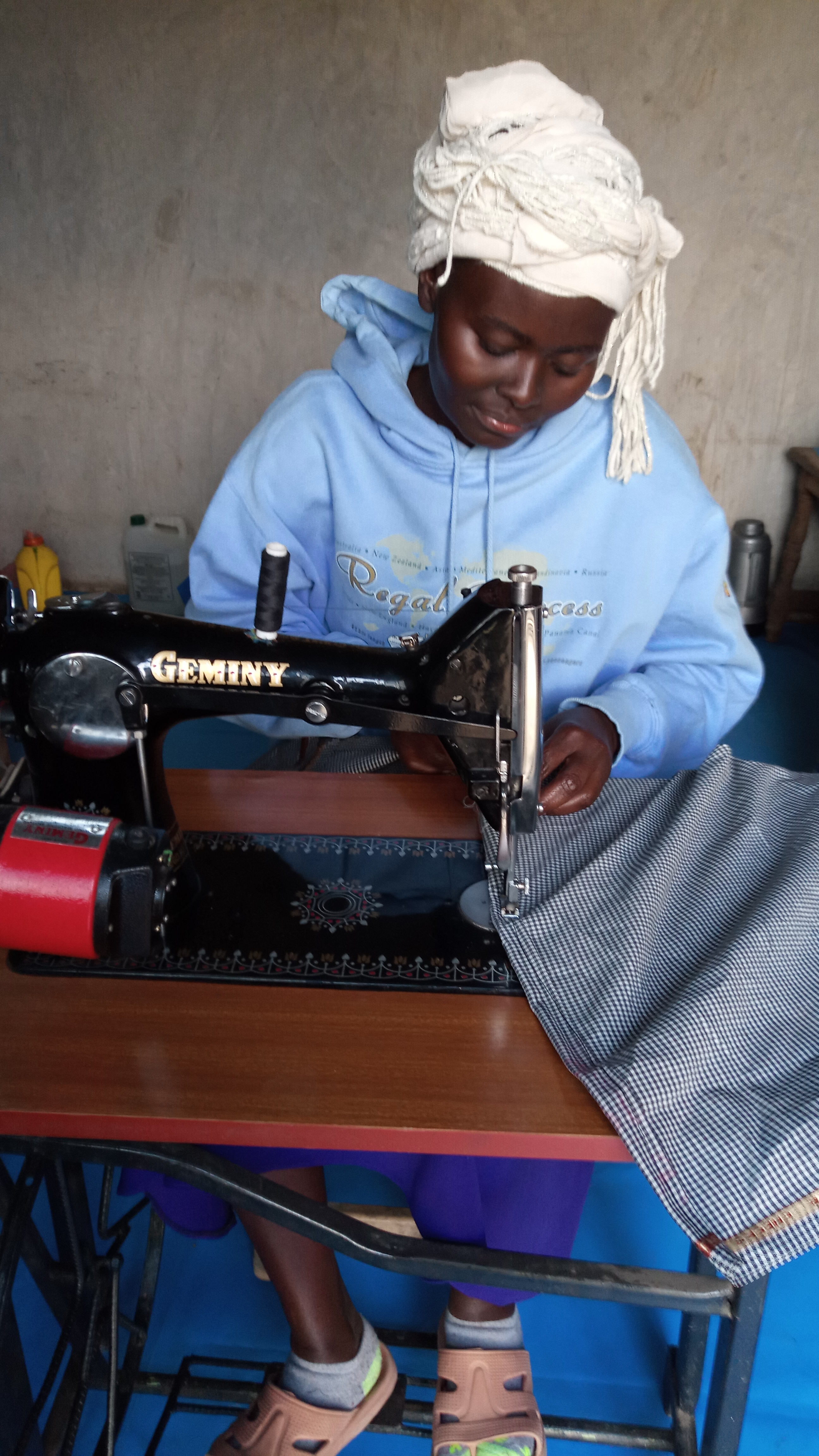 Mary Wangui sewing an apron with the sewing machine she received from Lady Hope