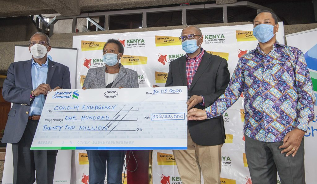 Standard Chartered CEO Kariuki Ngari presents a dummy cheque of KSh 12,000,00 million to Covid 19 emergency fund secretariat Chairperson Jane Karuku