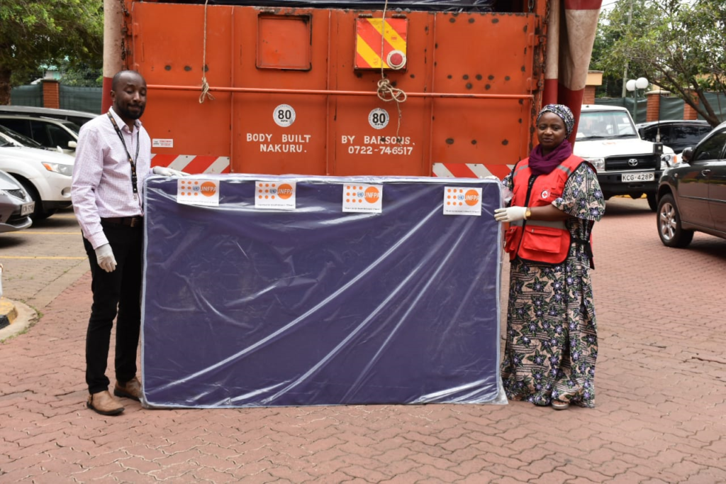 UNFPA Kenya Communication Specialist, Tom Ogola hands over mattresses and dignity kits to Kenya Red Cross Society - Secretary General, Dr. Asha Mohammed for distribution to West Pokot flood victims