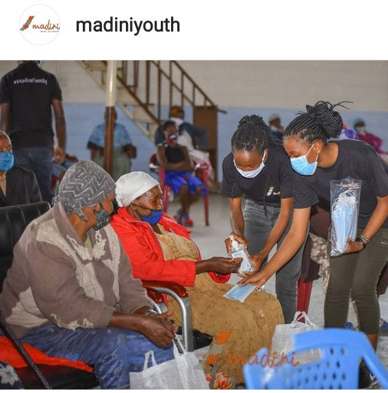 Madini youth foundation offering covid-19 safety measures by giving out masks and showing people how to sanitise in order to prevent the spread of covid-19