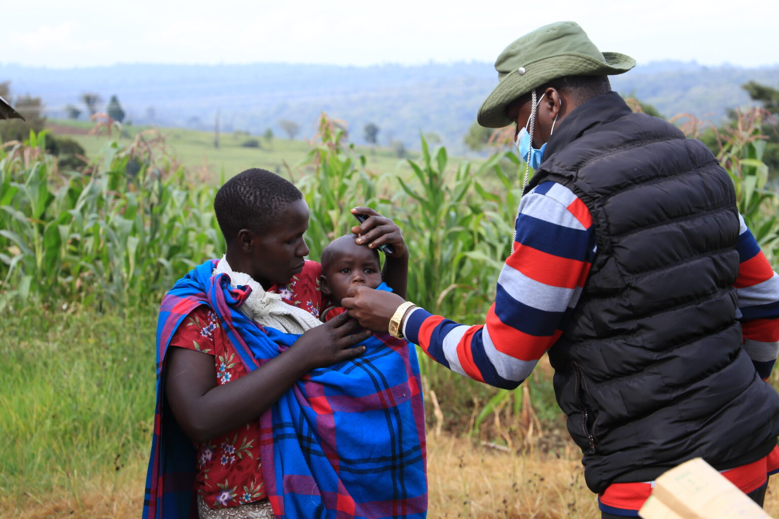 Mark, a community health volunteer, administers Vitamin A supplements and deworming tablets to children in Etereti village in Narok South, Narok County.