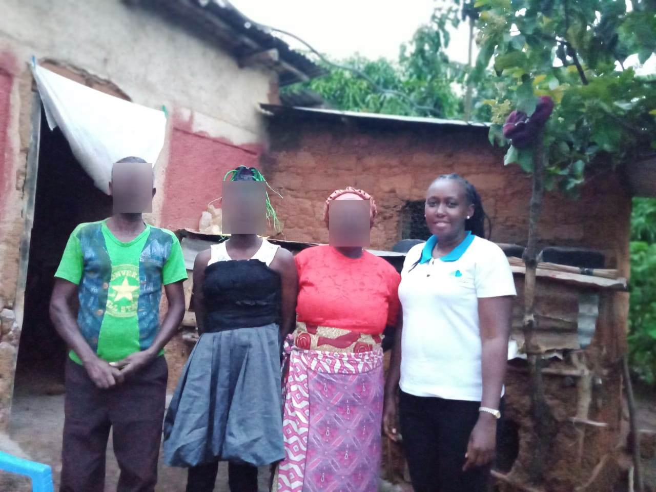 Mary Njoki* (second left) with her parents (left and second right). They are photographed with Clean Start's Mumbi Muguongo at their home during a family assessment visit. PHOTO. Rose Muthoni